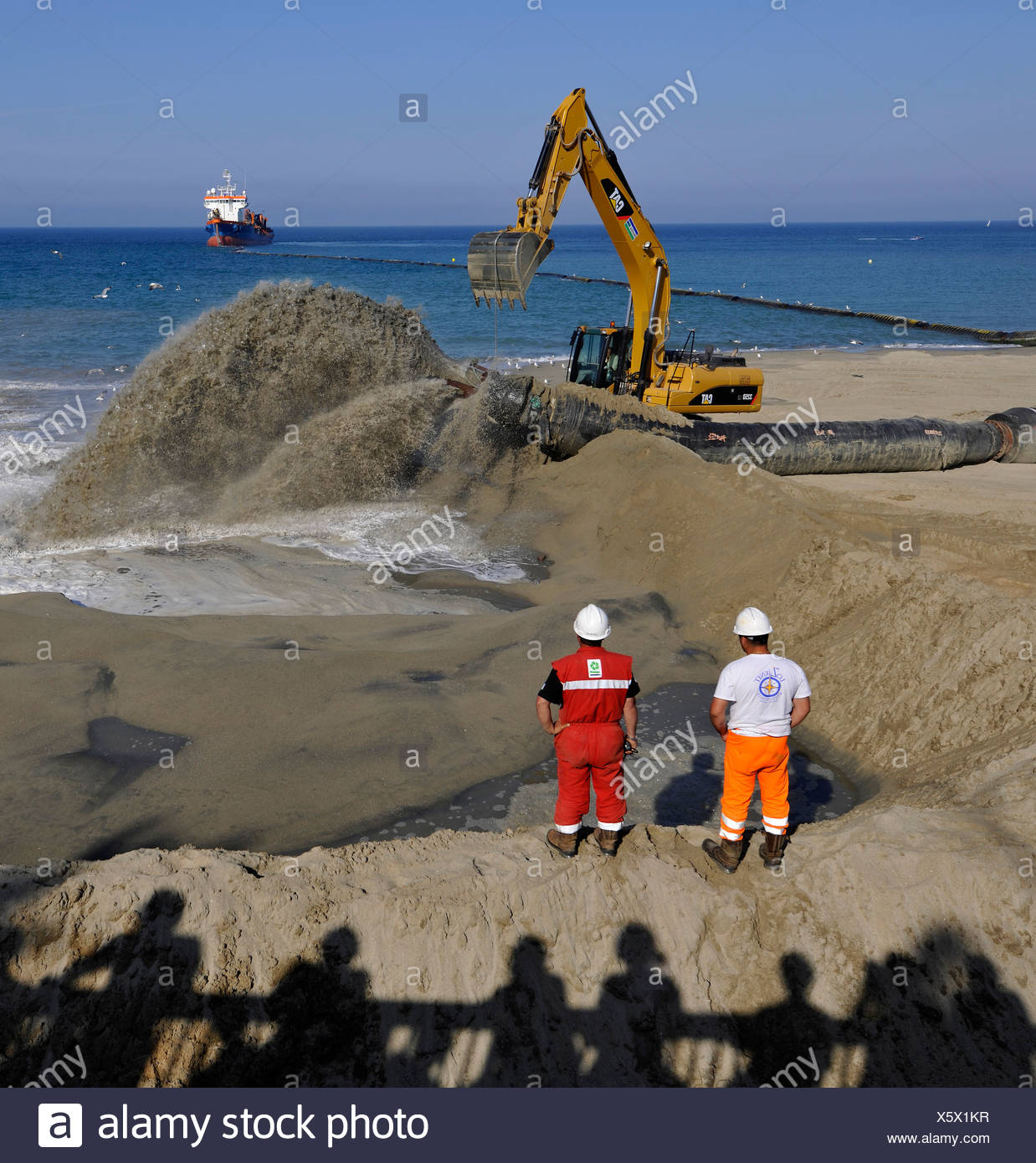 Onlookers watching while a dredger is pumping sand through a hose onto a beach for beach nourishment or beach replenishment - Stock Image
