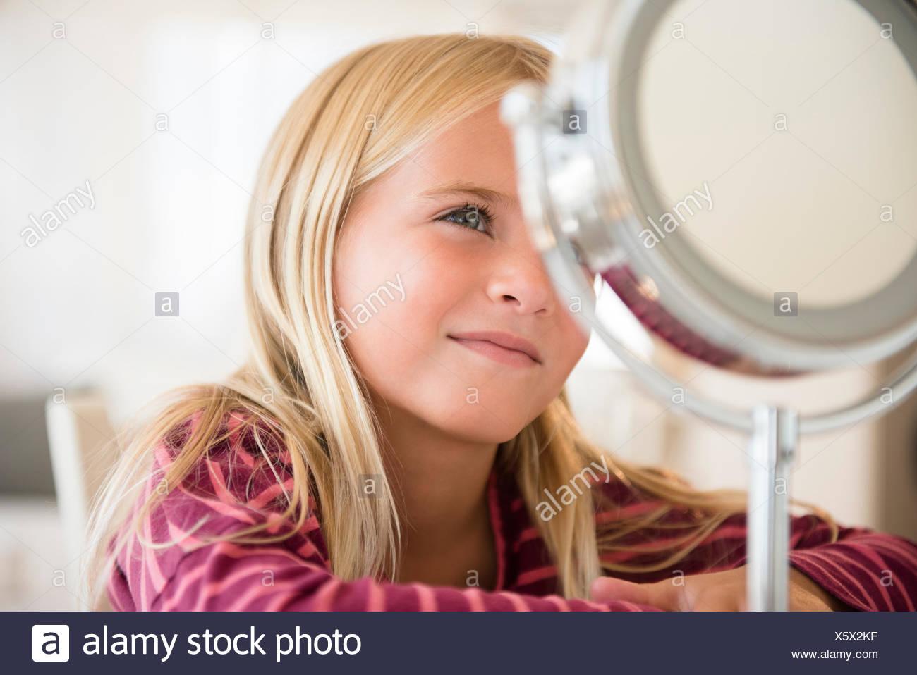 Girl (6-7) looking at vanity mirror - Stock Image