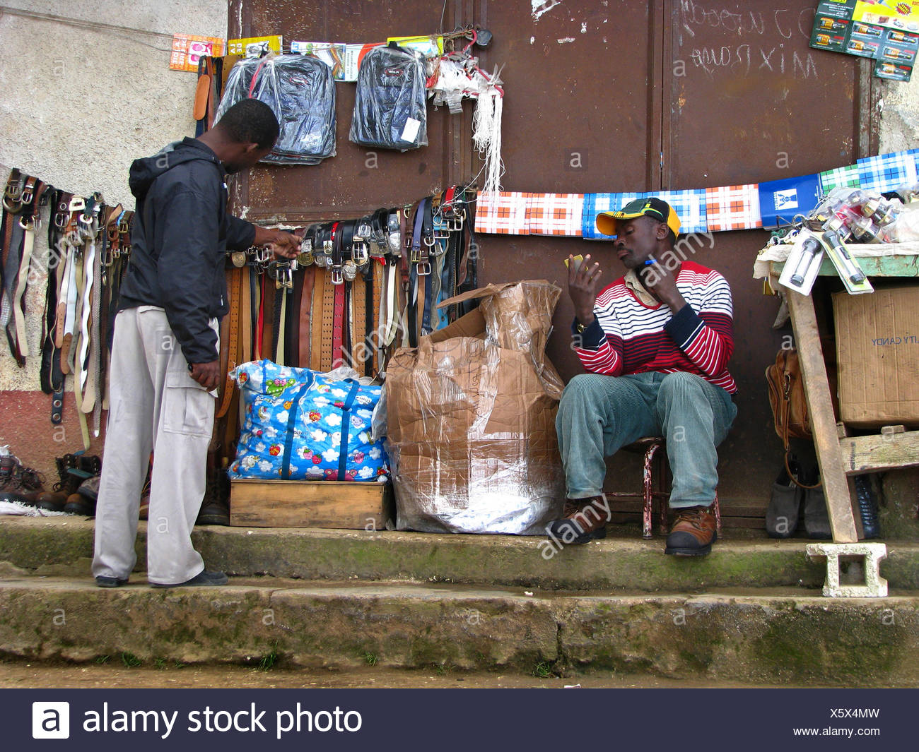 young man sitting at his general merchandise sales booth shaving dry, another , Haiti, Province de l'Ouest, Kenskoff, Port-Au-Prince - Stock Image