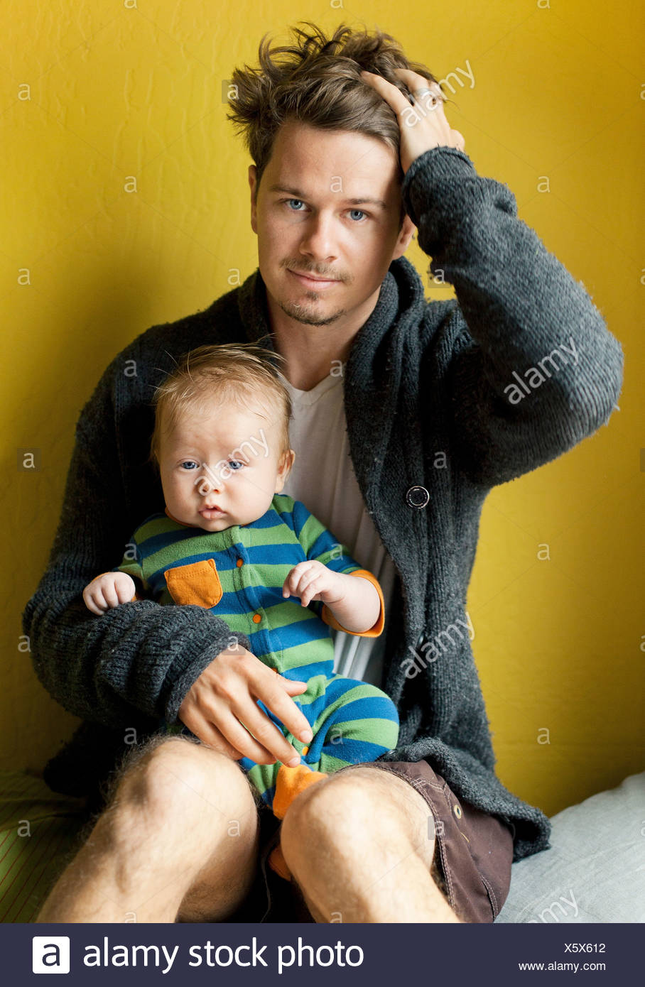 Tired father holding baby boy - Stock Image