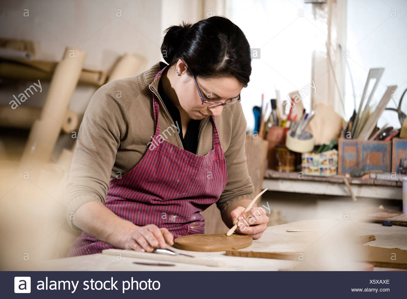 Craftswoman carving pattern into clay, Bavaria, Germany, Europe - Stock Image