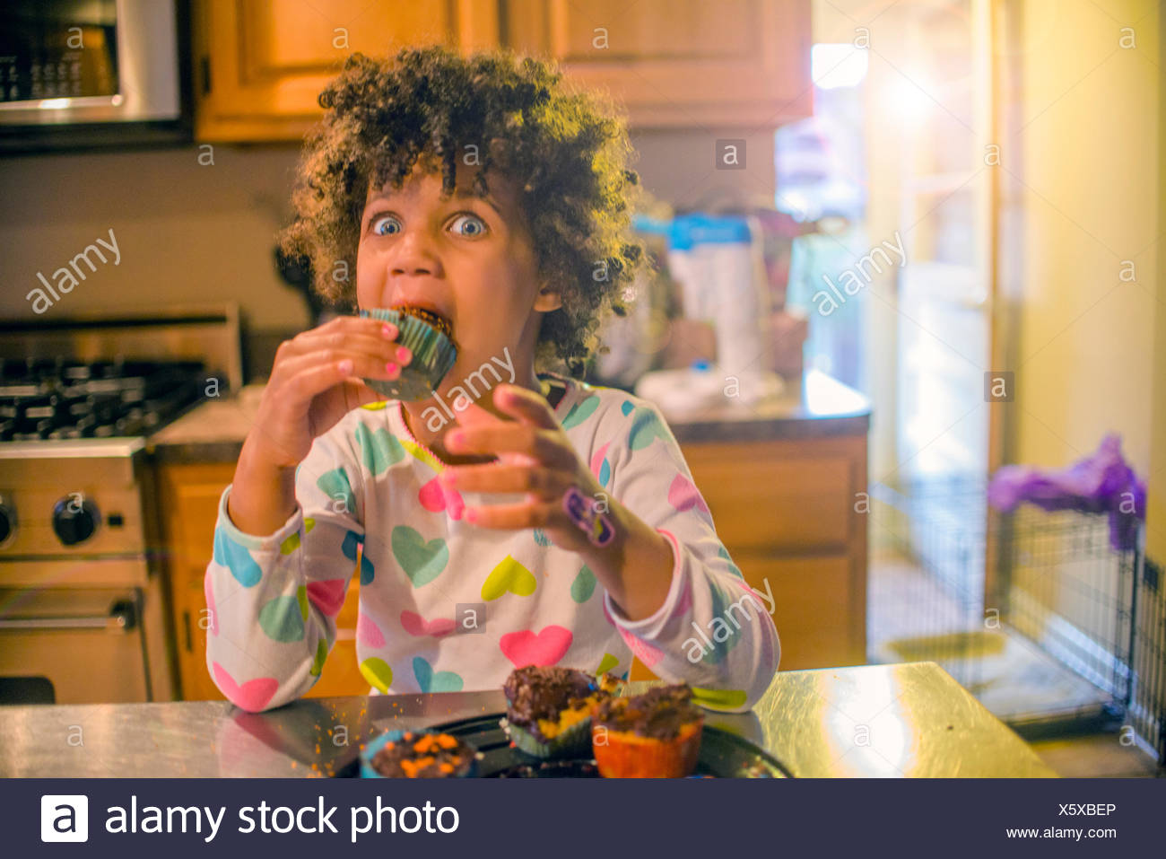 Portrait of surprised girl eating cupcakes at kitchen counter - Stock Image