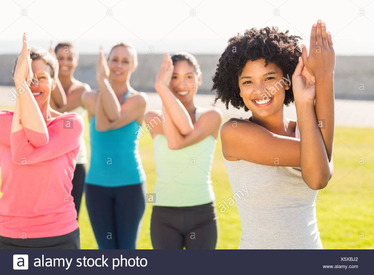 Smiling sporty women doing eagle pose in yoga class - Stock Image