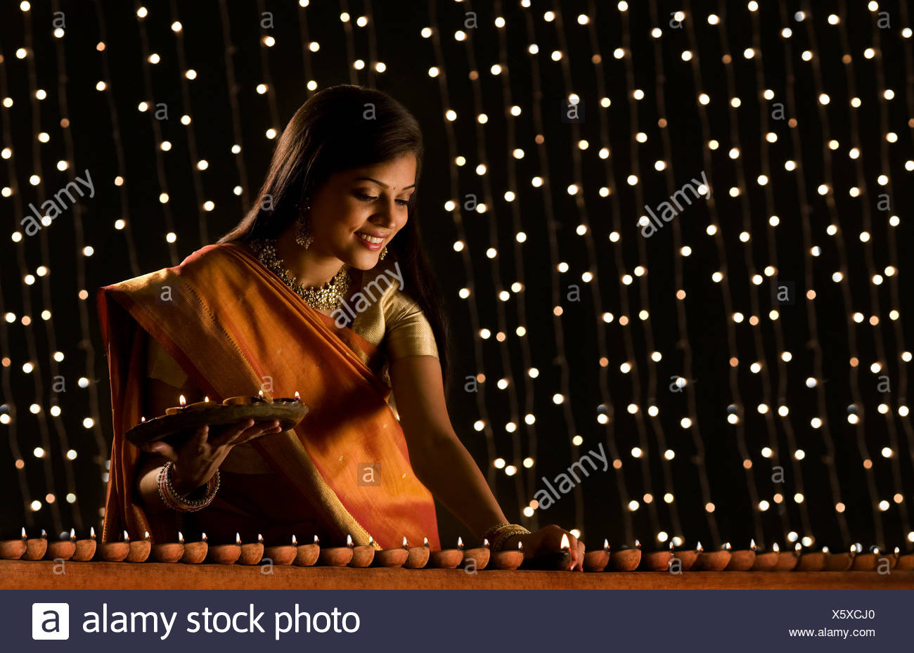 Woman arranging diyas Stock Photo