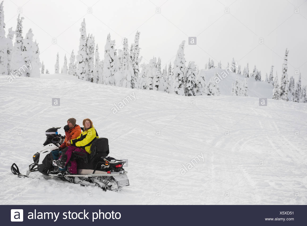 Couple sitting together on snowmobile during winter - Stock Image