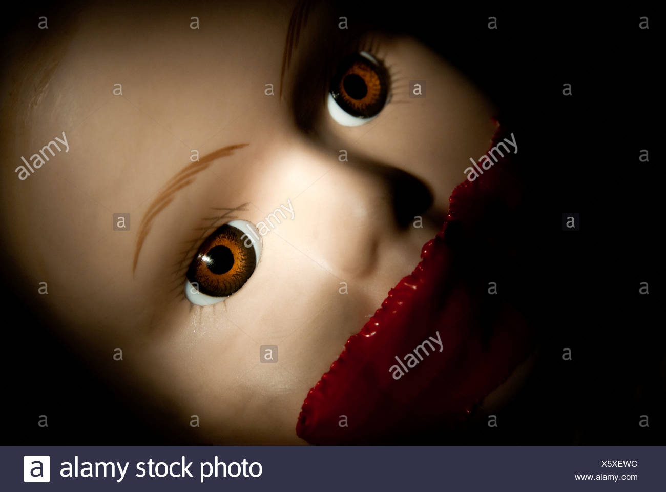 Close up of face of girl doll with red tape on mouth - Stock Image
