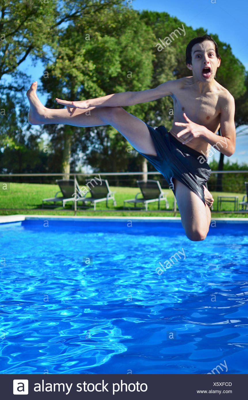 Boy jumping into swimming pool - Stock Image