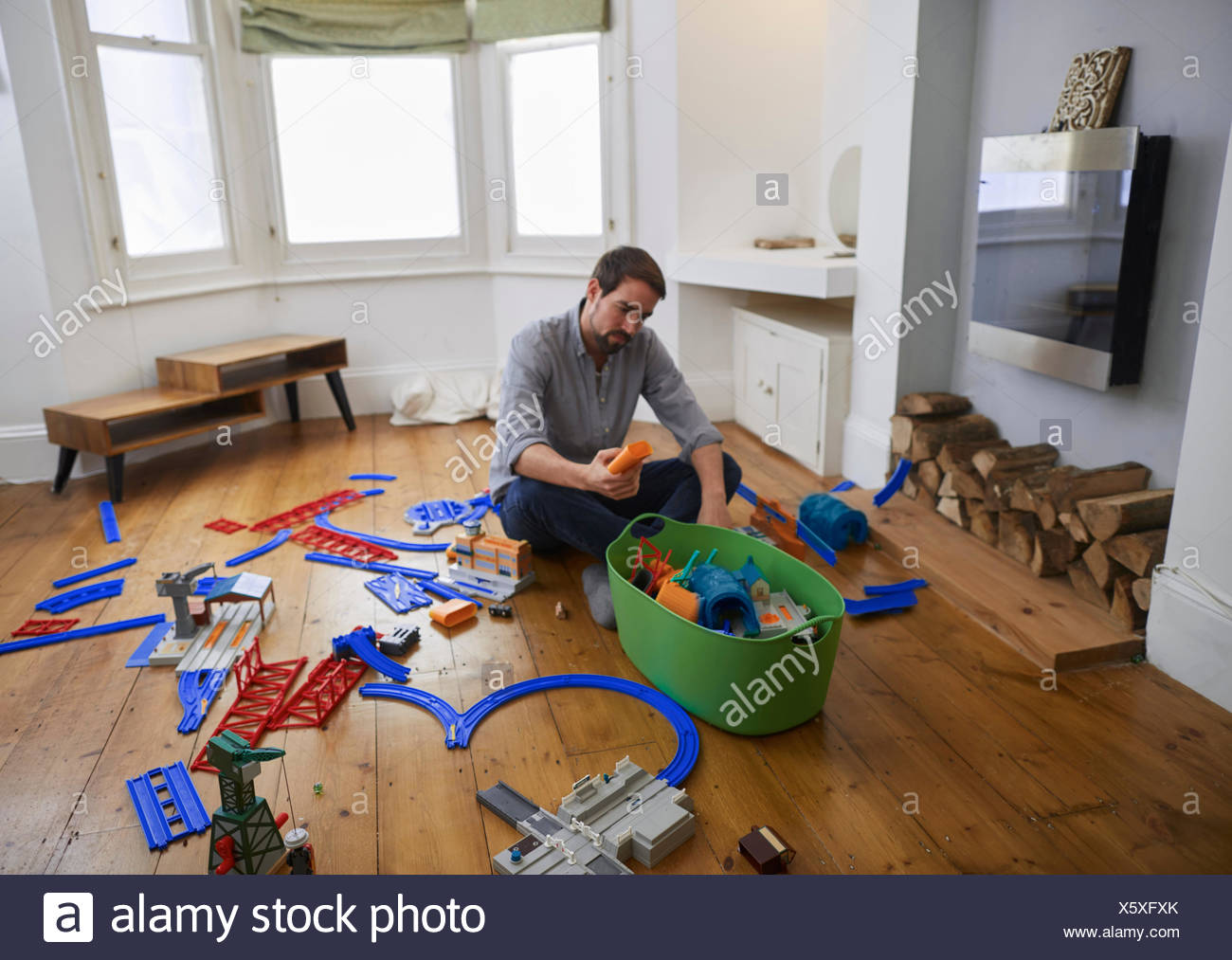 Mid adult man contemplating toys scattered in living room - Stock Image