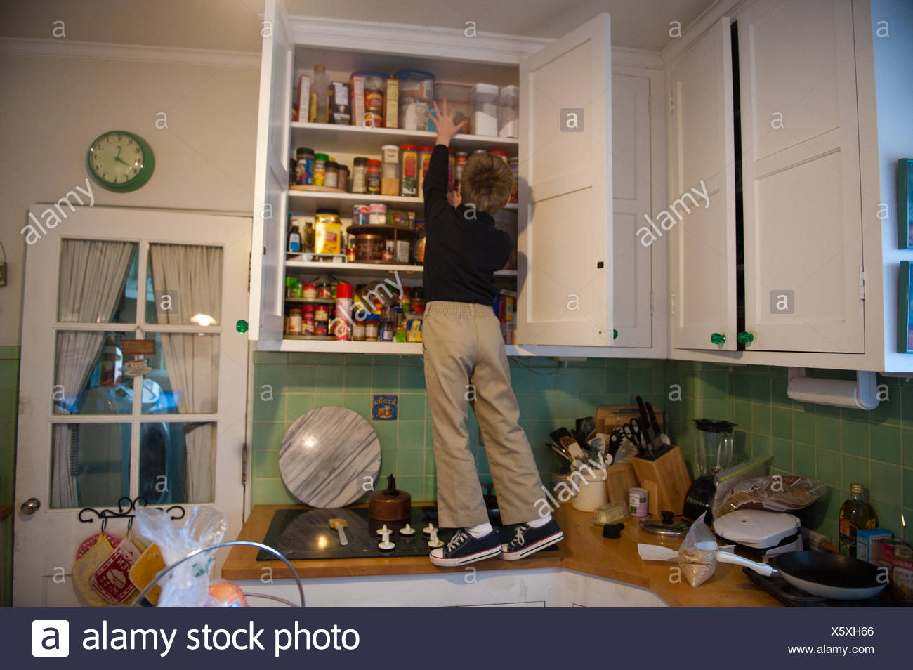 A young boy searches for goodies that are kept in a hard to reach spot at his home in Lincoln, Nebraska. - Stock Image