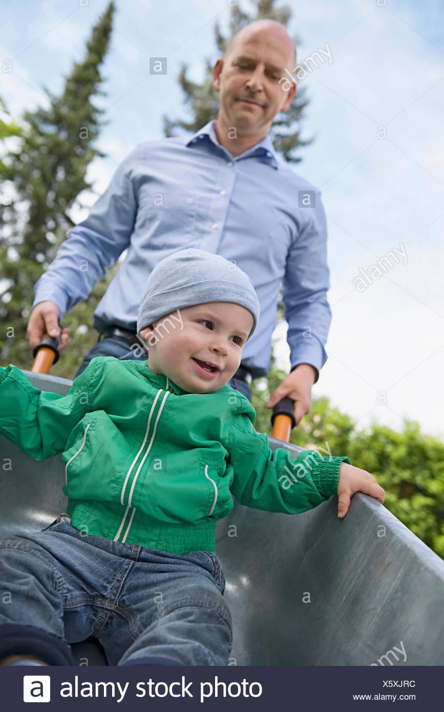 Father Pushing Son In Wheelbarrow Stock Photos Father
