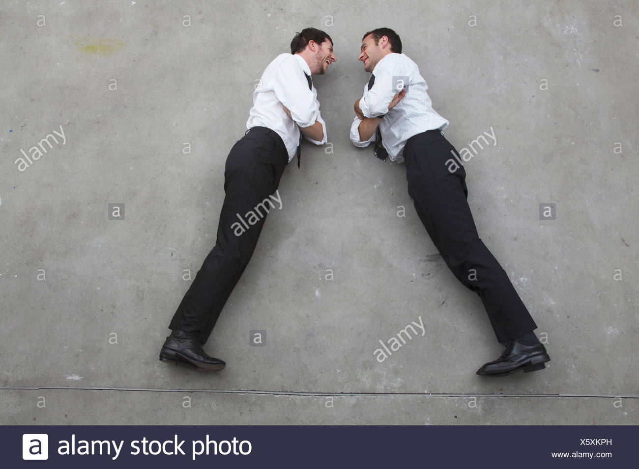 Two businessmen standing opposite to opposite, portrait, elevated view - Stock Image