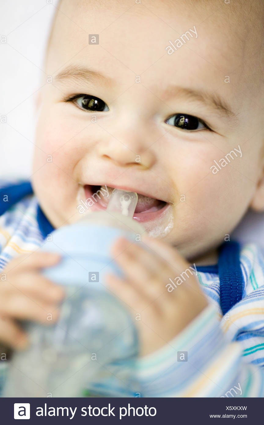6 months old eurasian boy bottle feeding, Montreal, Quebec, Canada - Stock Image