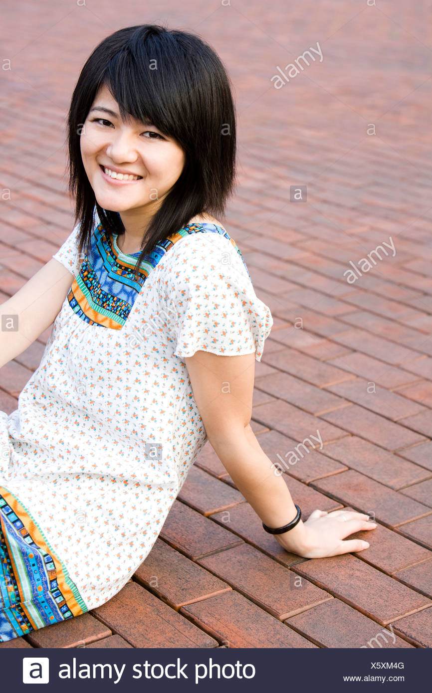 Young woman sitting on ground - Stock Image