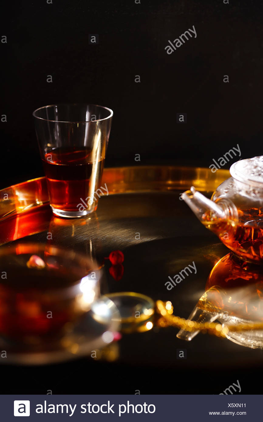 Small glass teapot and glasses with hot black tea, dried rose petals, pocket magnifier on golden chain on golden tray. Evening light. - Stock Image