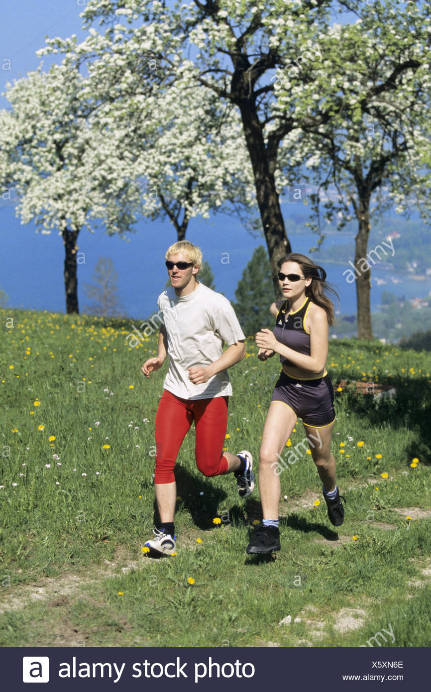young pair jogging over field path in spring - Stock Image