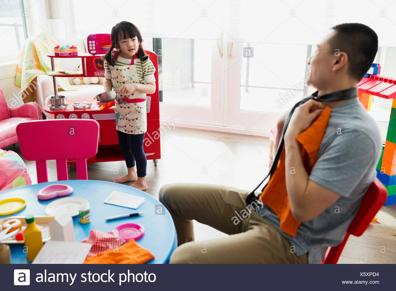 Father and daughter playing pretend restaurant - Stock Image