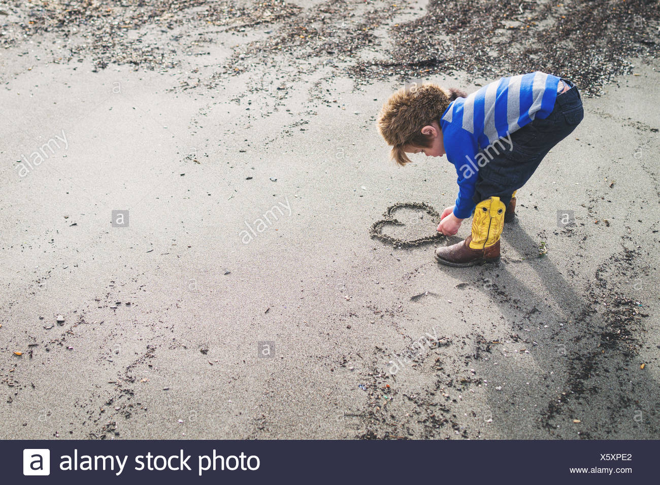 Boy in cowboy boots and raccoon hat drawing a heart in the sand - Stock Image