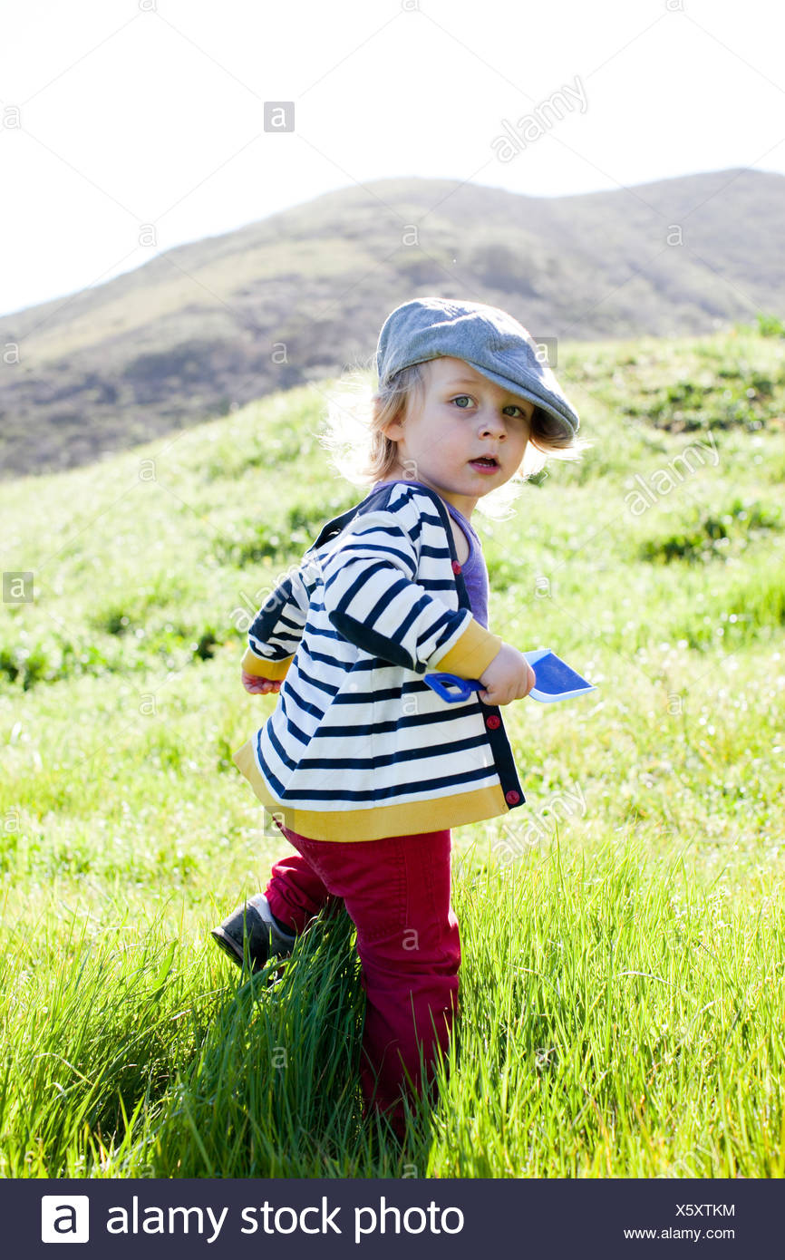 Portrait of male toddler looking back while toddling in grass - Stock Image