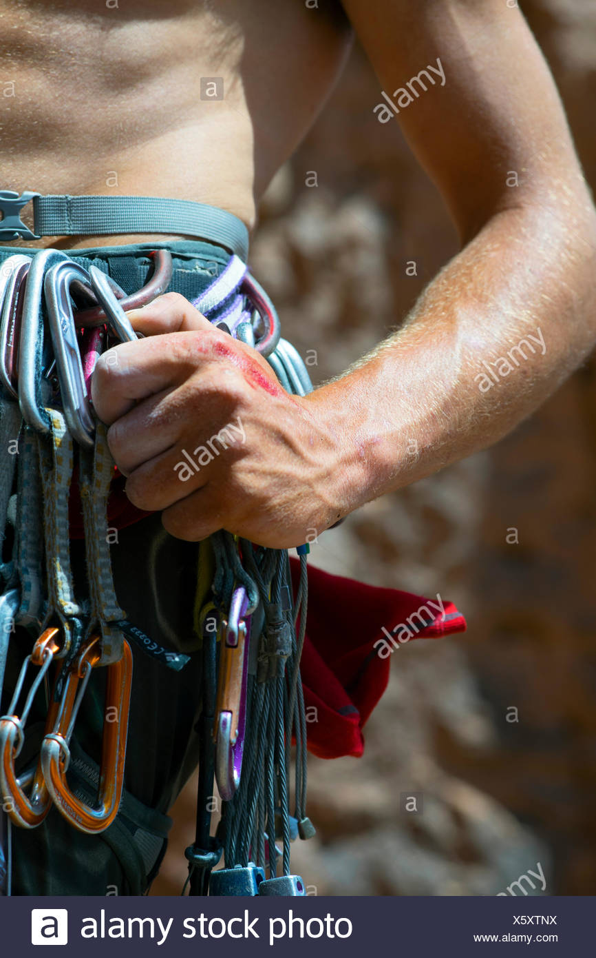 A close up of a climber's hand grabbing gear while climbing a route in Todra Gorge in the Atlas Mountains of Morocco Africa. - Stock Image