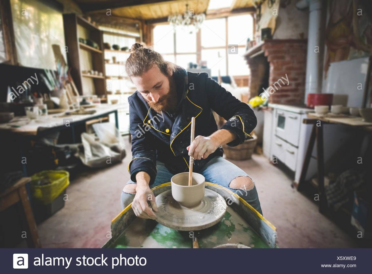 Bearded mid adult man in workshop sitting at pottery wheel using diddler to make clay pot - Stock Image