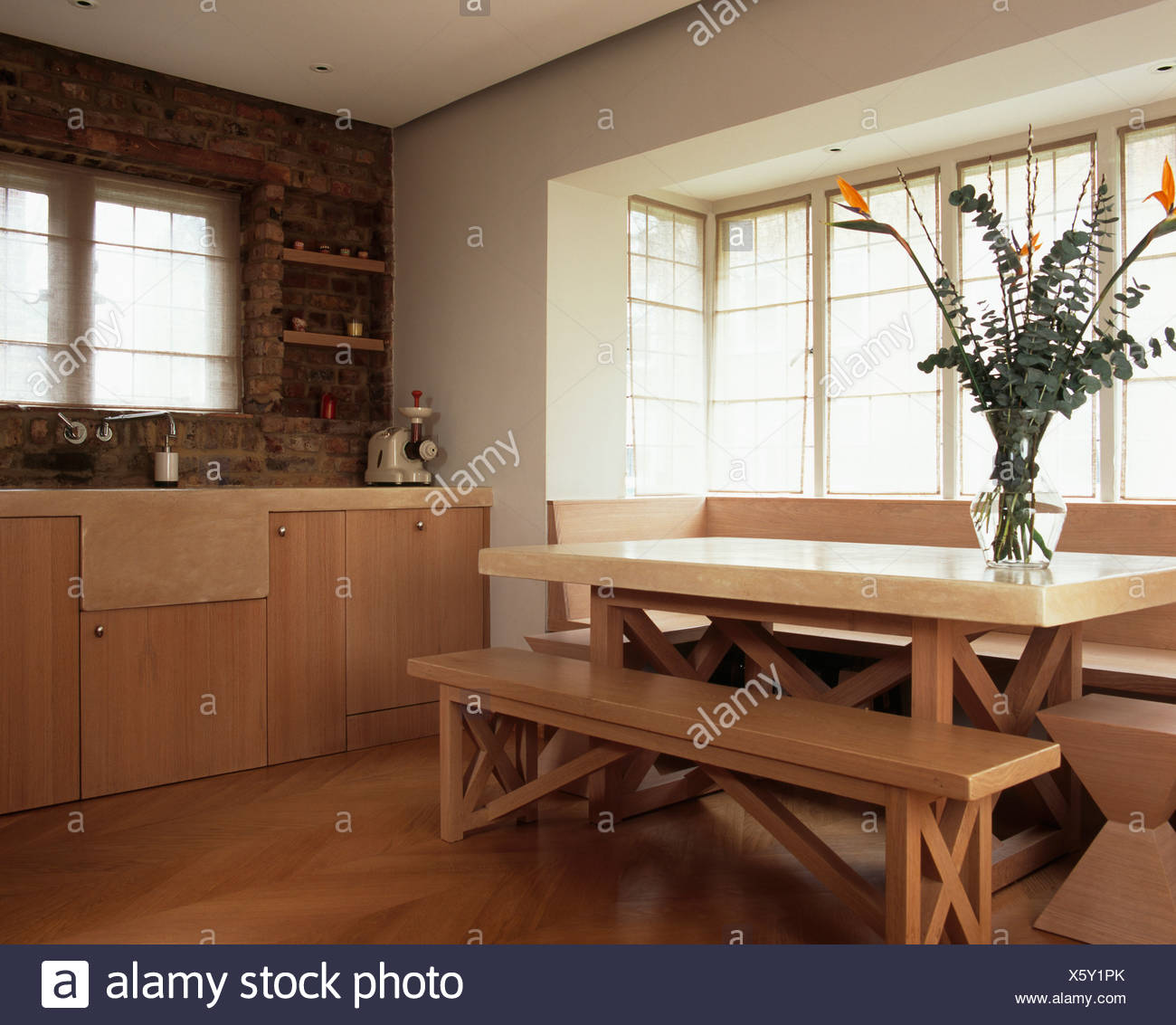Melamine Topped Table And Simple Wood Benches In Front Of Window In Modern Country Kitchen Stock Photo Alamy