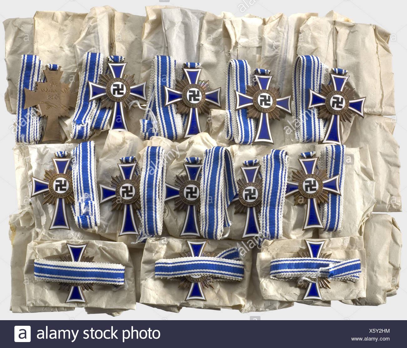 50 Mother's Crosses in Bronze, of the firm Deschler & Son. All are with ribbons, in original tissue papers, and in outstanding, unworn condition (OEK 3515). From a Munich attic find. Cf. Hermann Historica auction 53, lots 3128 to 3131. historic, historical, 1930s, 1930s, 20th century, awards, award, German Reich, Third Reich, Nazi era, National Socialism, object, objects, stills, medal, decoration, medals, decorations, clipping, cut out, cut-out, cut-outs, honor, honour, National Socialist, Nazi, Nazi period, Additional-Rights-Clearences-NA - Stock Image