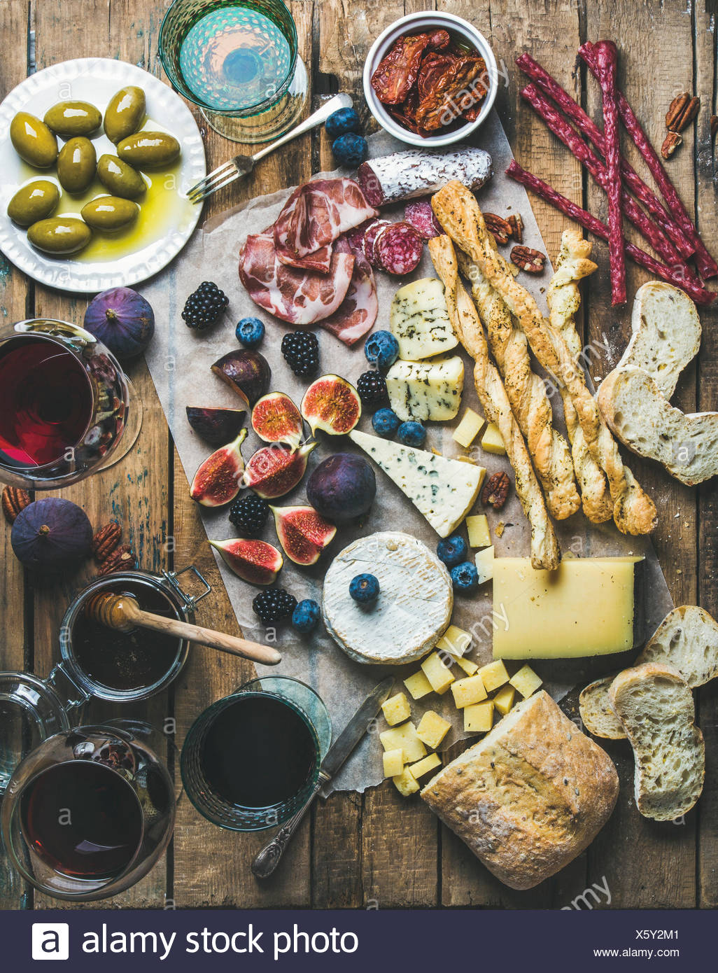 Wine and snack set with various wines in glasses, meat variety, bread, green olives, sun-dried tomatoes, figs, nuts and berries - Stock Image