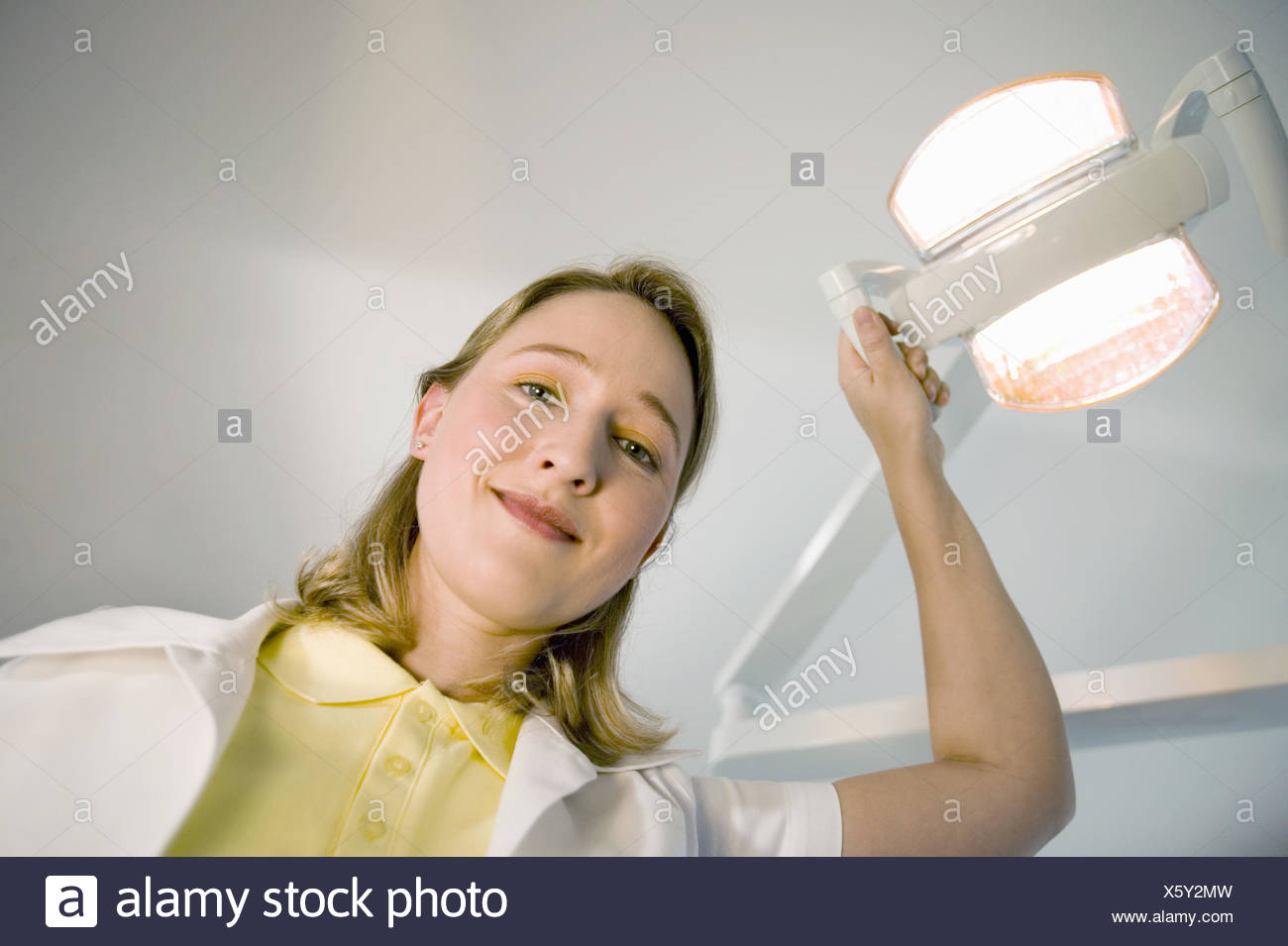 Female dental assistant smiling and adjusting dental light - Stock Image