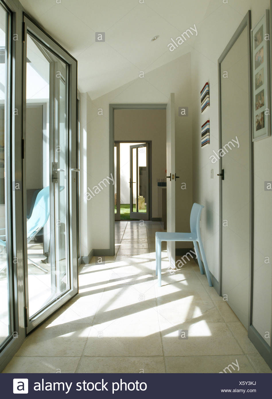 Glass bi fold doors in modern hall with pale blue chair and glass bi fold doors in modern hall with pale blue chair and limestone flooring planetlyrics Choice Image