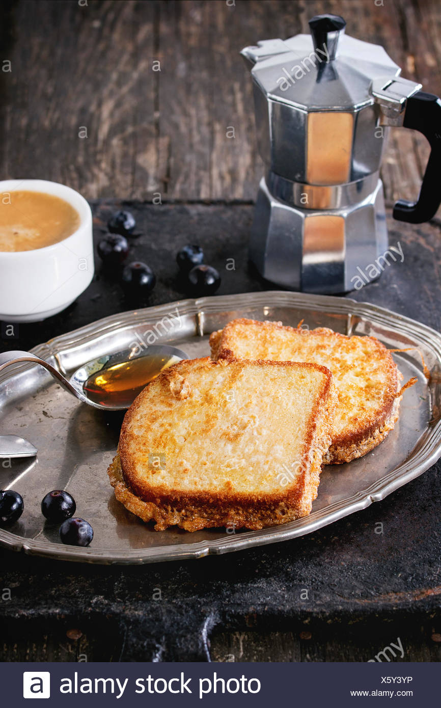 Breakfast theme. Grilled Toasts with honey, blueberries, cup of coffee espresso and coffee pot, served on vintage tray over old - Stock Image