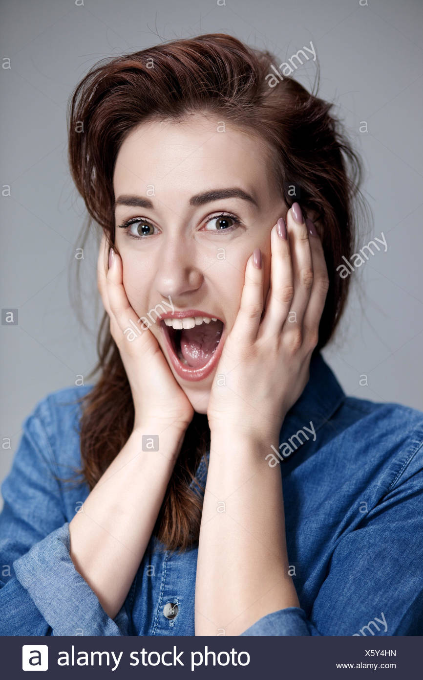 Portrait of young woman with shocked facial expression - Stock Image