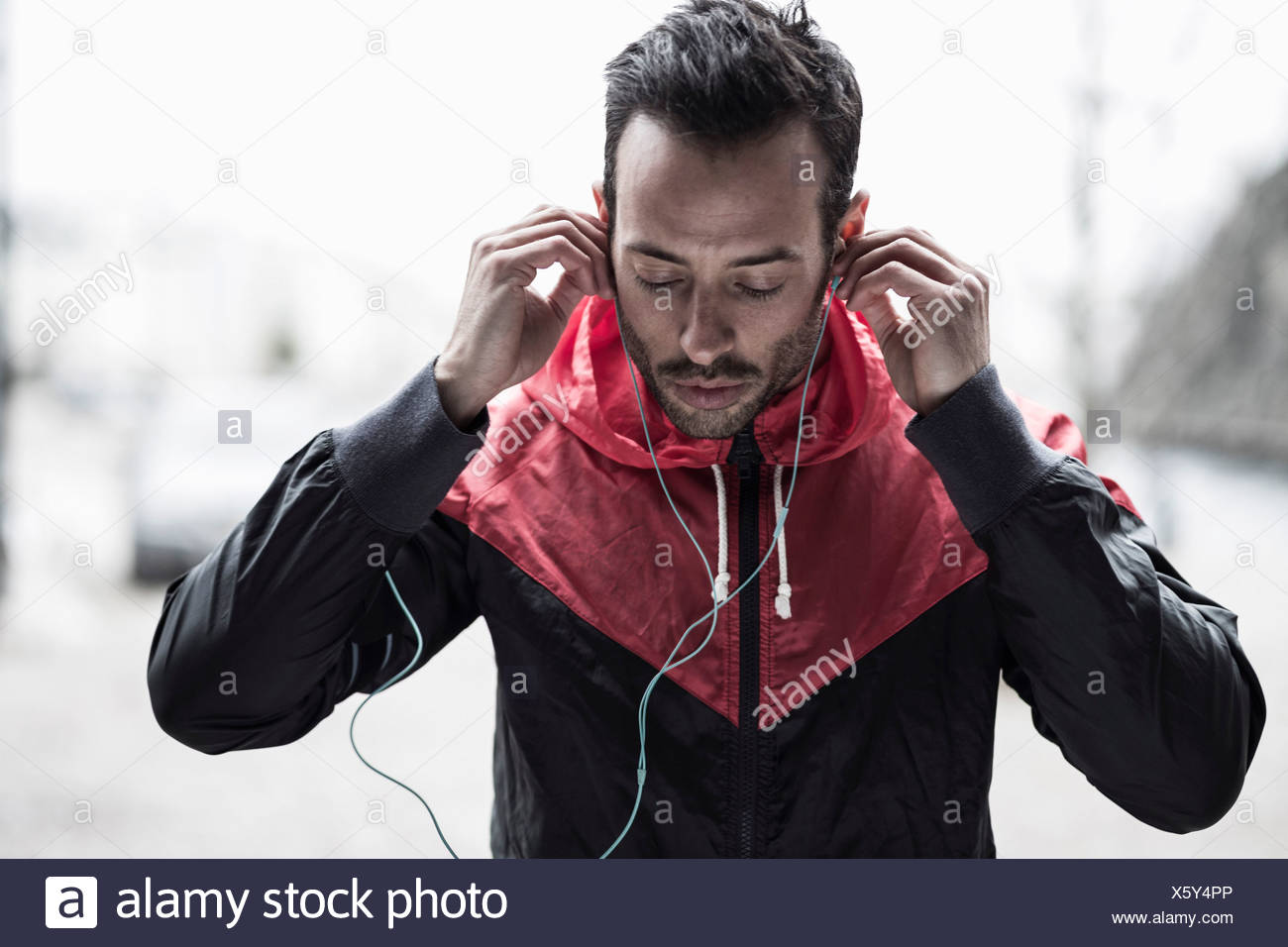 Sporty man in jacket adjusting headphones - Stock Image