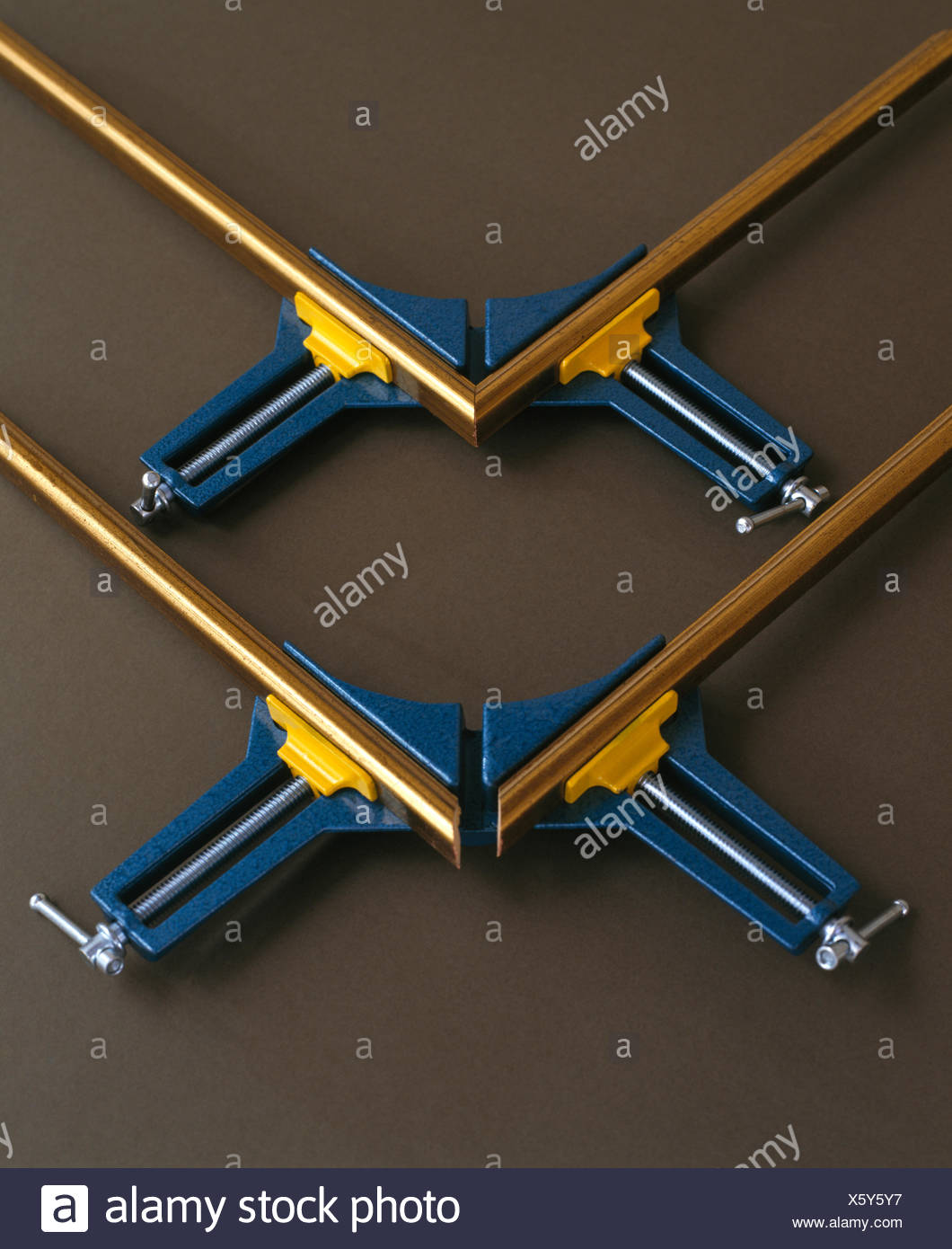 Close-up of gilt picture frames held in metal vices Stock Photo
