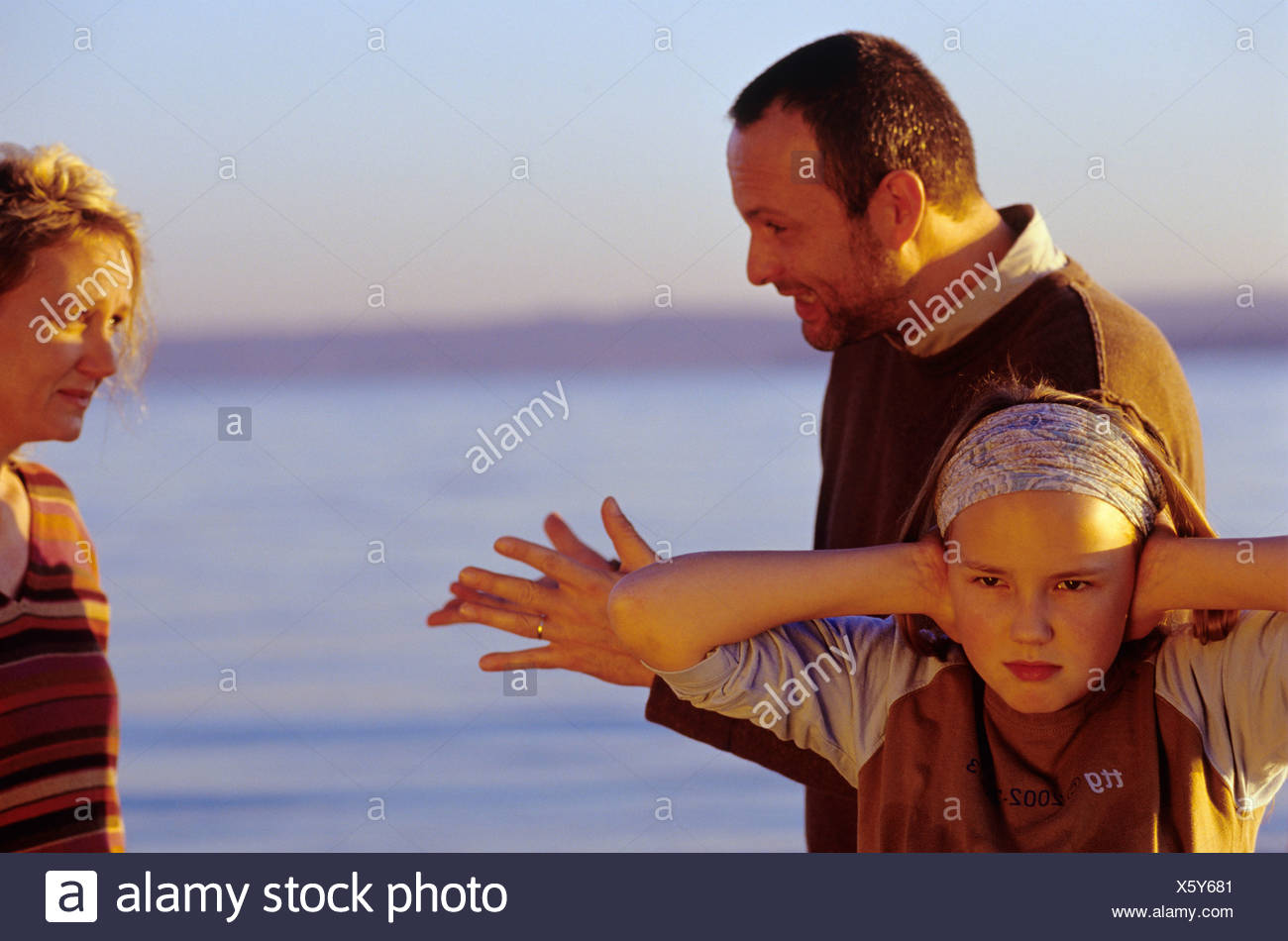 Parents in argument, girl (10-11) covering ears at beach Stock Photo