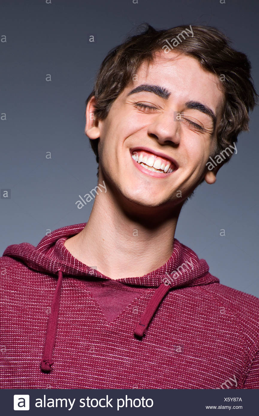 Young man laughing with eyes closed, studio shot - Stock Image