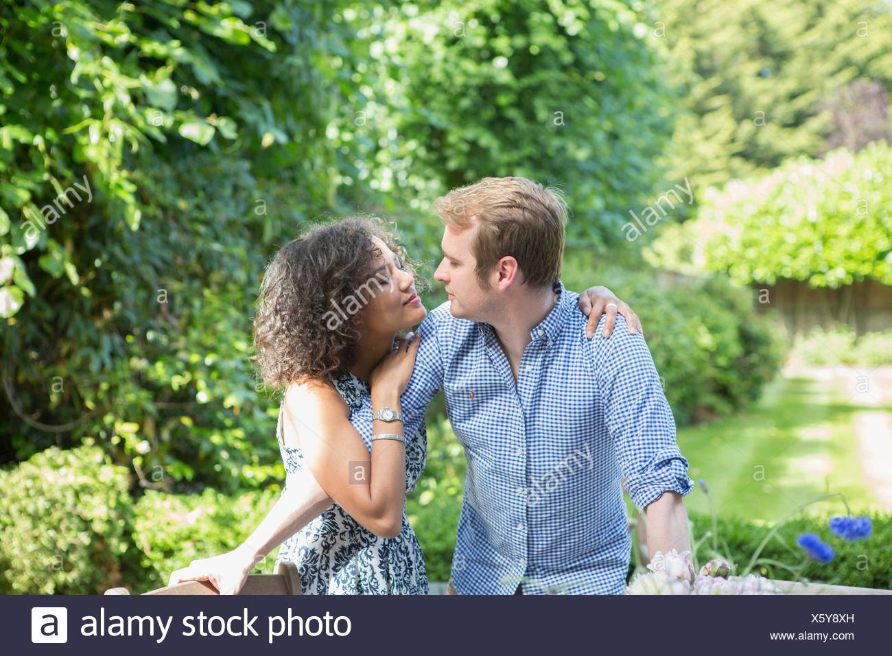 Mid adult couple, outdoors, embracing, face to face - Stock Image
