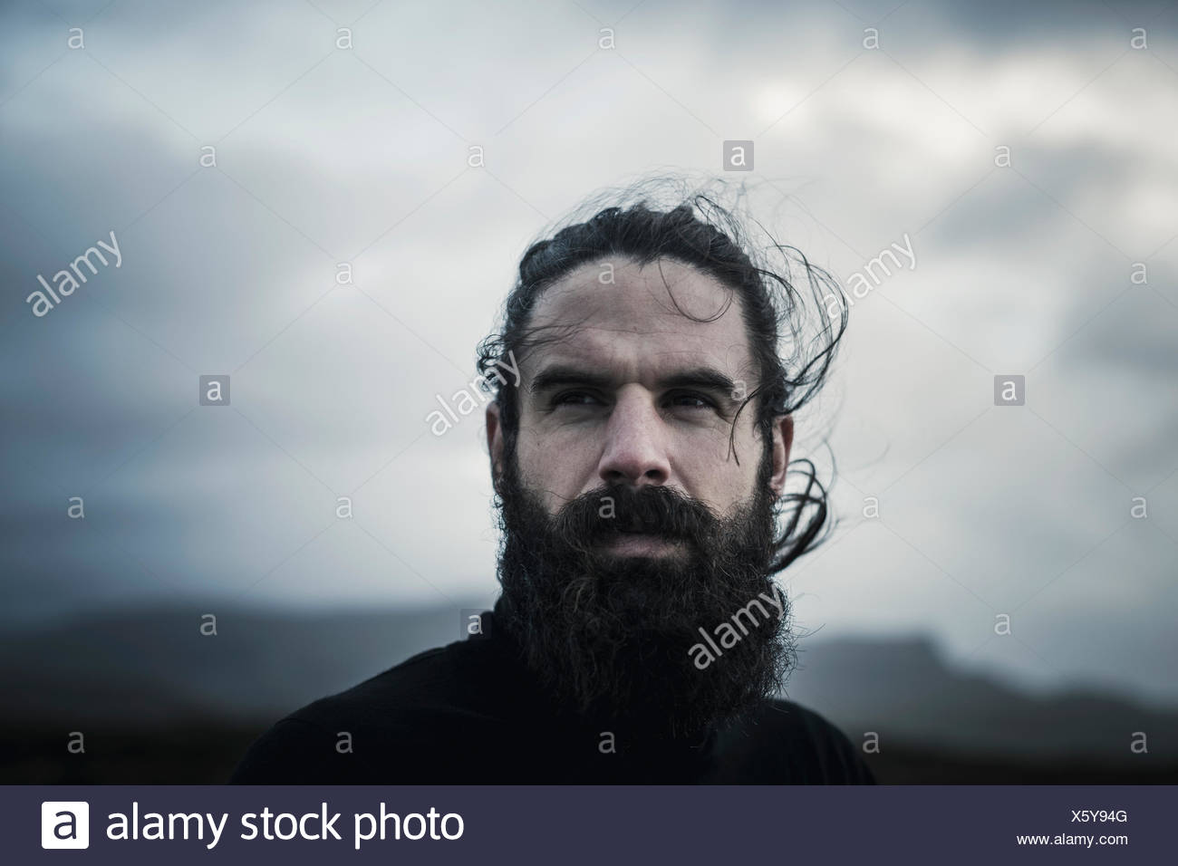 A man with black hair, a full beard and moustache. - Stock Image
