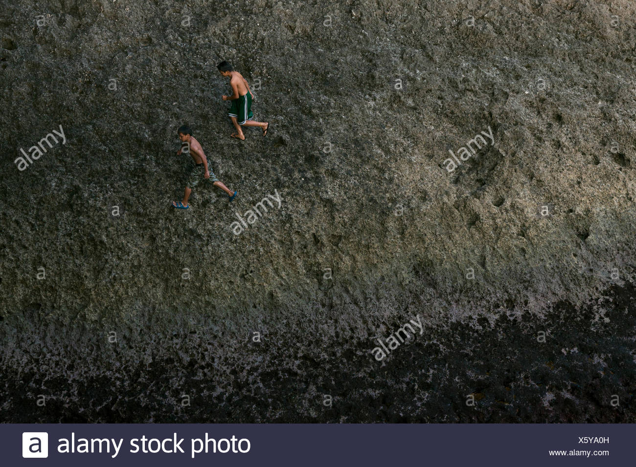 Ivatan children playing by the pier after school. The small islands in Batanes are surrounded by water, which becomes a source of both livelihood and recreation. - Stock Image