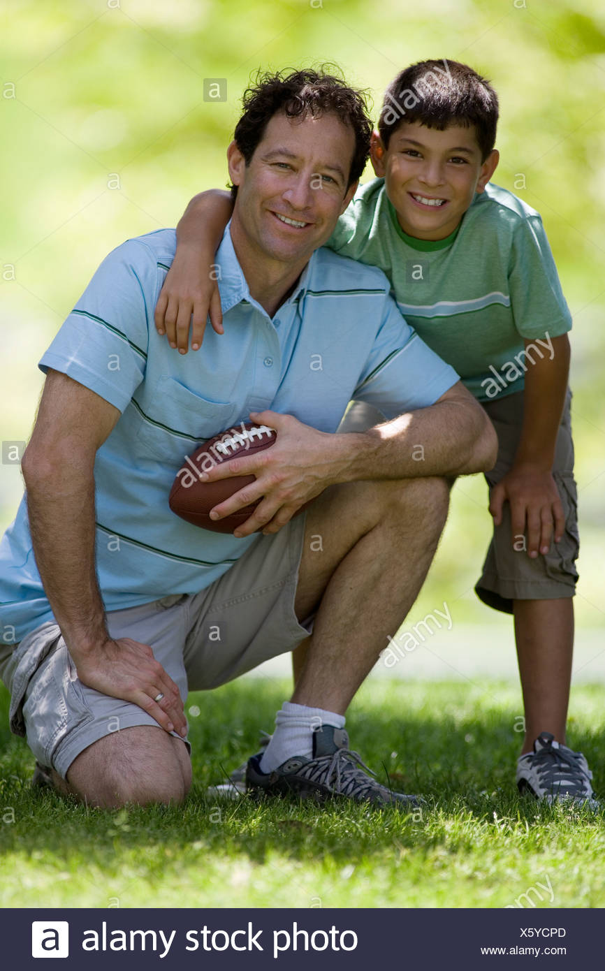 Father crouching beside son 10 12 on grass in park holding american football smiling portrait - Stock Image