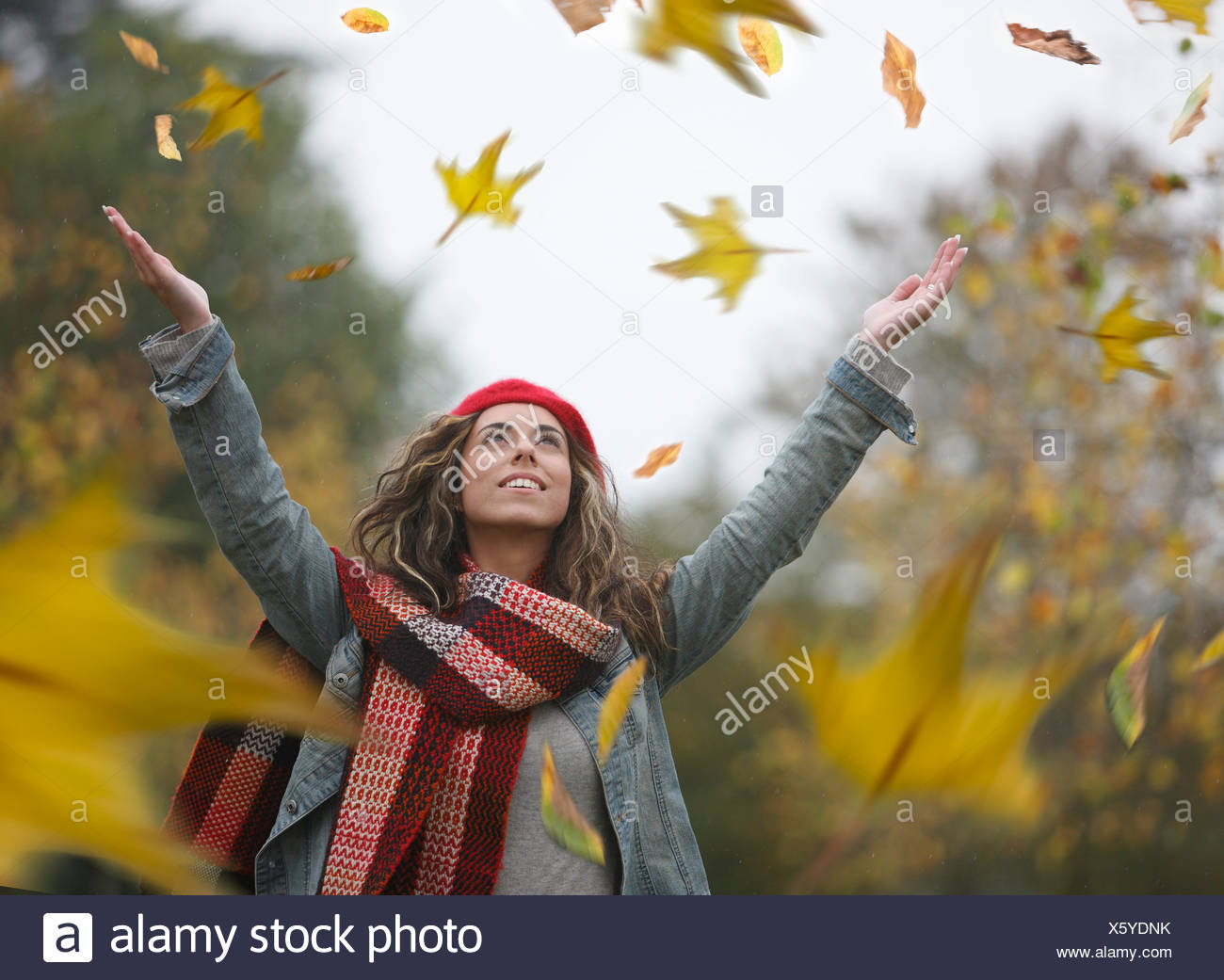 Woman throwing dried leaves into air - Stock Image