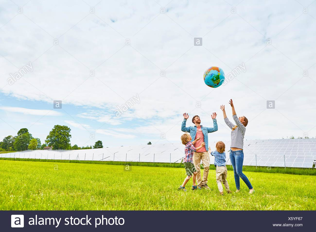 Young family playing with inflatable ball, on field, next to solar farm Stock Photo