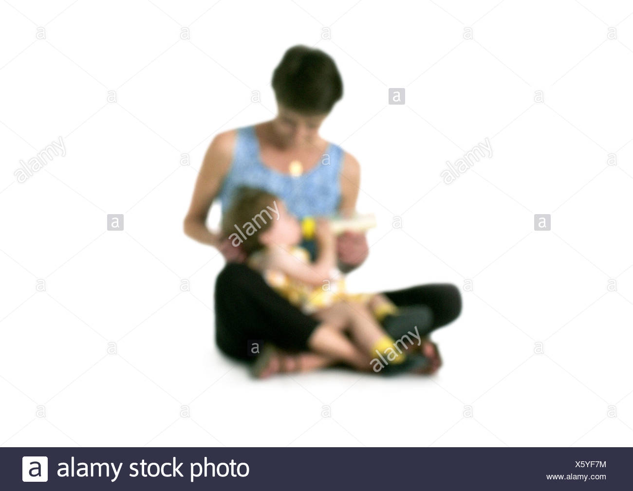 Silhouette of woman feeding bottle to girl on lap, on white background, defocused - Stock Image