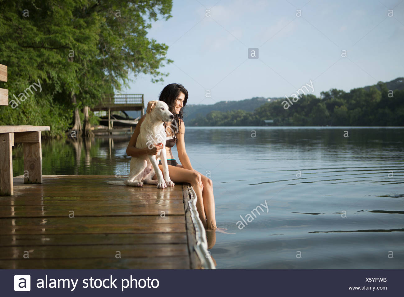 A woman with her arm around a small white dog on a jetty on a lake. Stock Photo