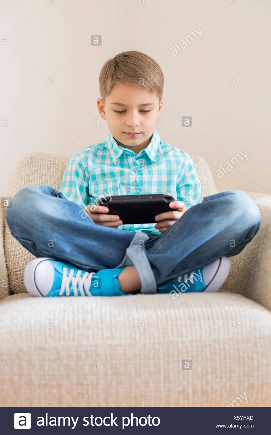 Boy playing hand-held video game on sofa at home - Stock Image