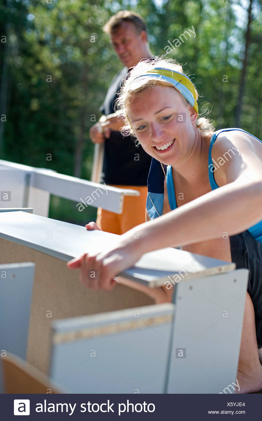 Woman mounting shelf - Stock Image