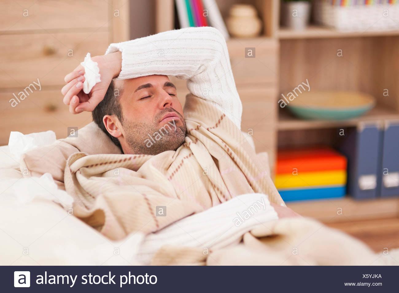 Man lying on the sofa, sick - Stock Image