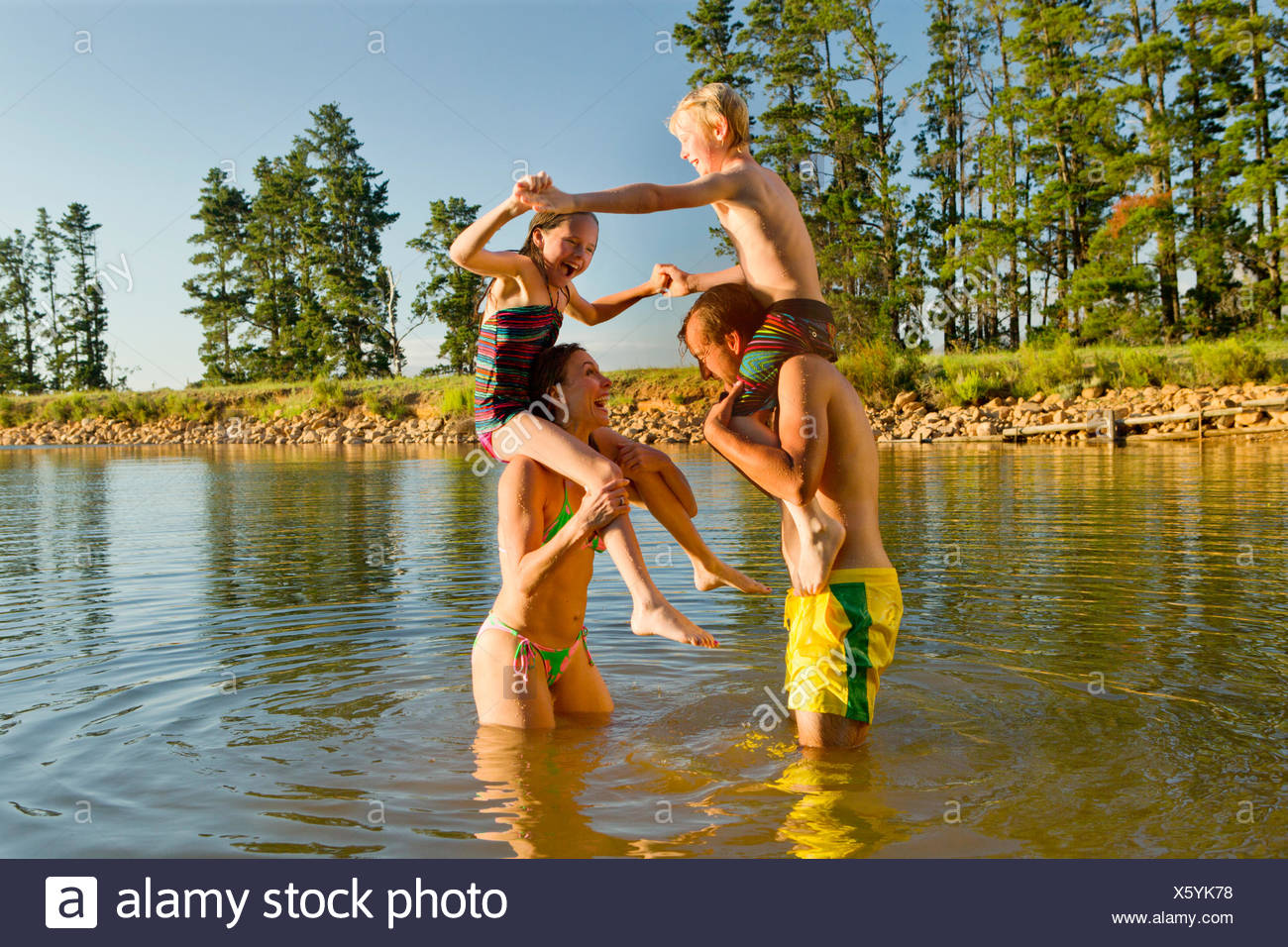 Happy couple with children on shoulders, having water fight in lake - Stock Image