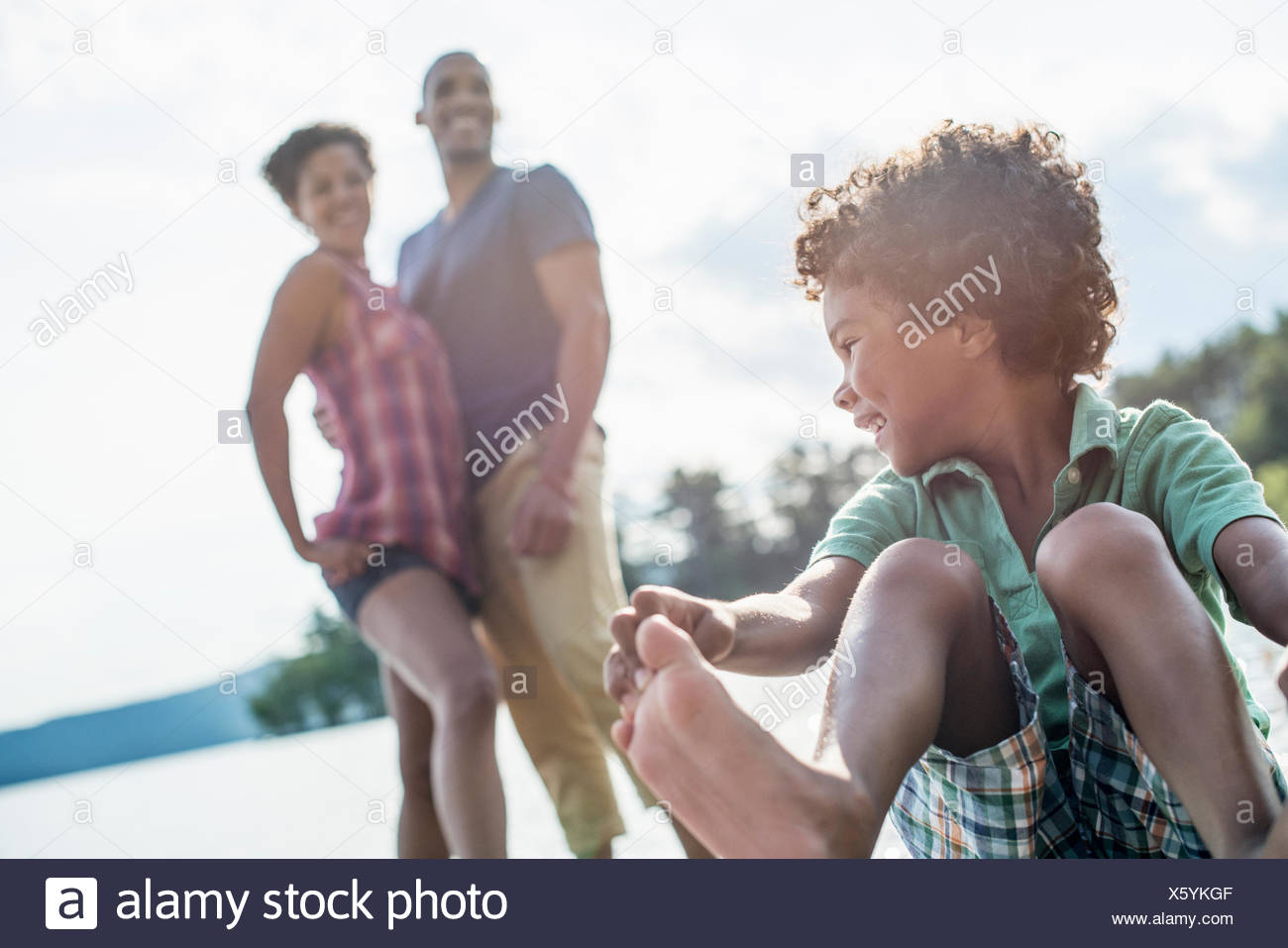 A family, parents and son by a lake in summer. - Stock Image