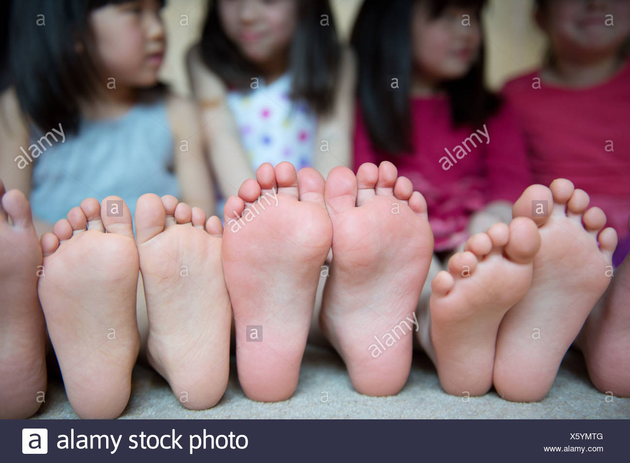 Girls sitting together with barefeet in a row - Stock Image