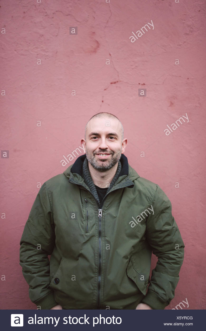 Portrait of smiling bald man standing in front of a wall - Stock Image